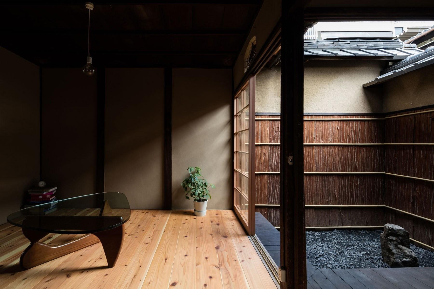 居間・濡れ縁・坪庭が連続的に繋がる町屋らしい空間。塀の杉皮は貼り替えている。 | 昭和小路の長屋|賃貸向け京町家の改修