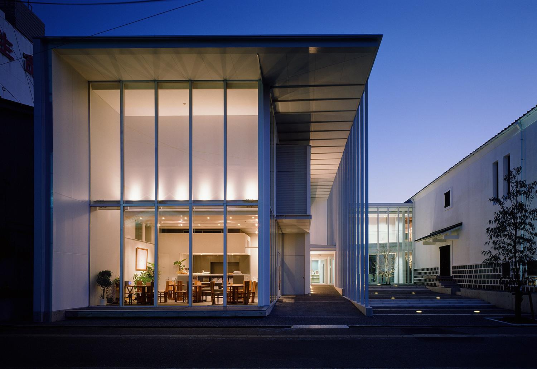 北から見た夕景。新設棟は鉄骨とガラスのシンプルな構成。新設棟の北側(写真手前)は、民間が運営するカフェ。 | 小松市立宮本三郎美術館