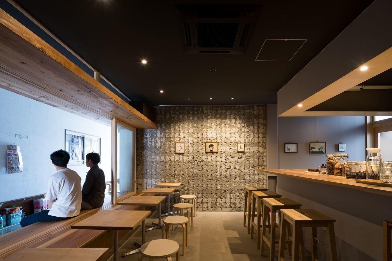 縁側(写真左)の引戸をあけると縁側とカフェが繋がります。ミニギャラリーとなる正面の壁は、かつて市場だったころのタイルの跡が残るモルタル。写真:西川公朗 | 脇町珈琲 ― 縁側のある小さなカフェ ―