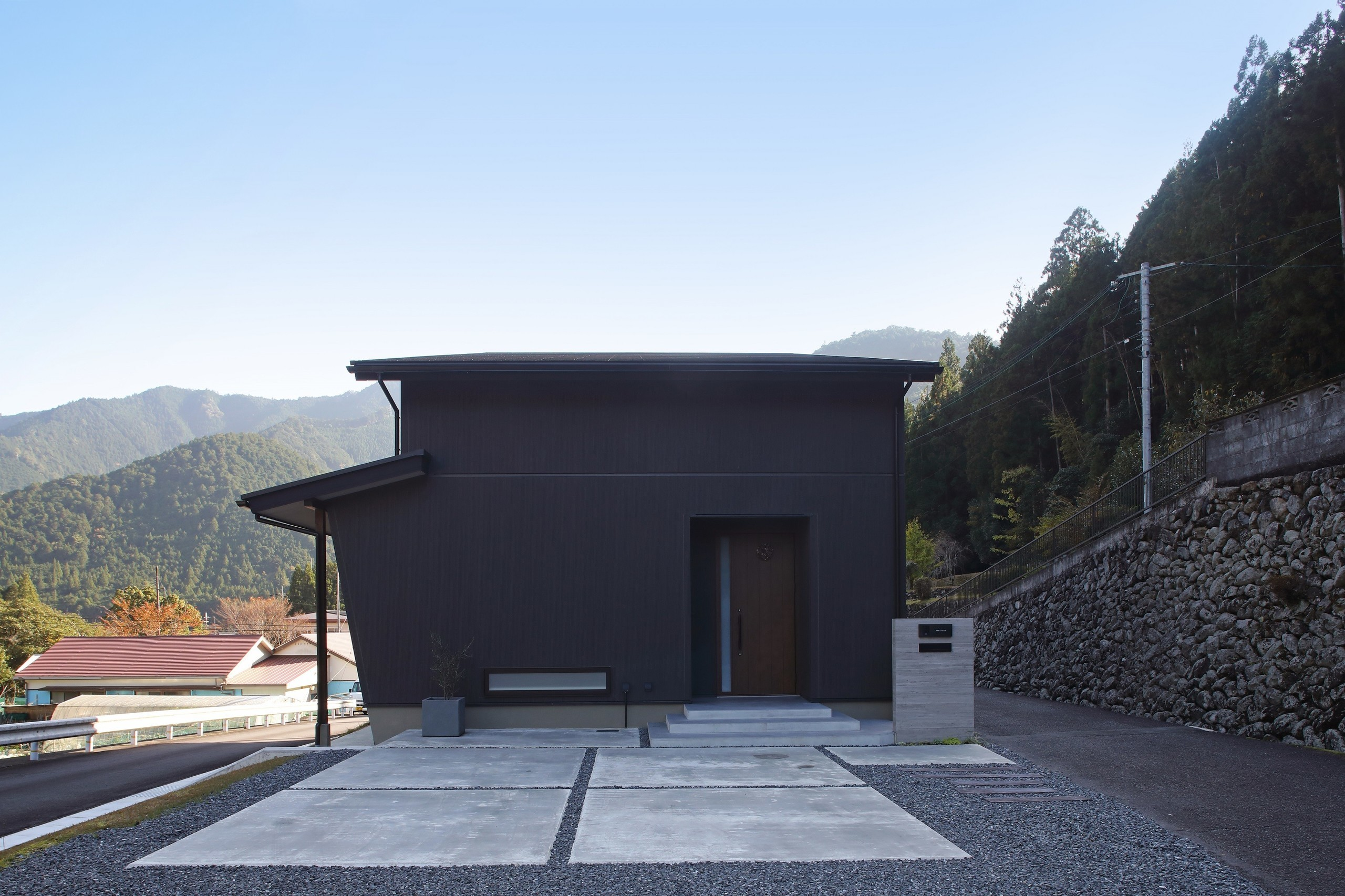 郊外に佇む借景とアウトドア空間のあるシンプル和モダンの家の建築事例写真