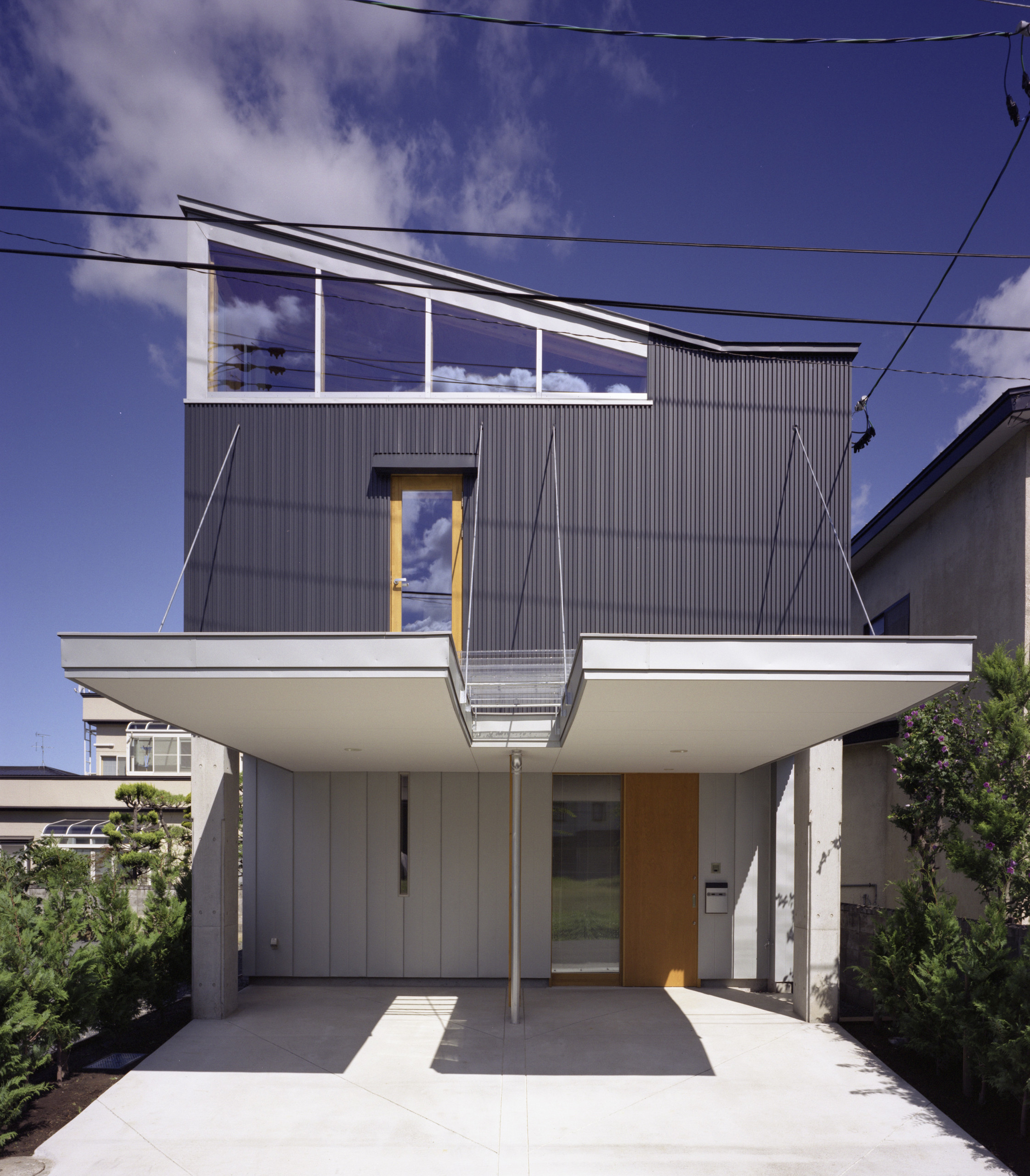 道路側外観 駐車スペースの屋根を二分したのは、建築面積を抑えるため 2階正面ドアは、ピアノ搬入のため  | 南城西の家 ピアニストの家