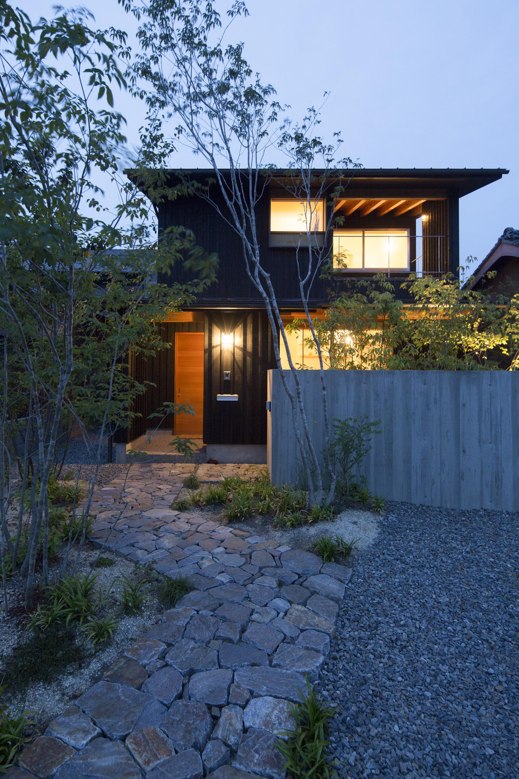 墨色の押縁板壁の外壁 地元幡豆産の石敷アプローチ | 寺津の家/墨色の押縁板壁の家