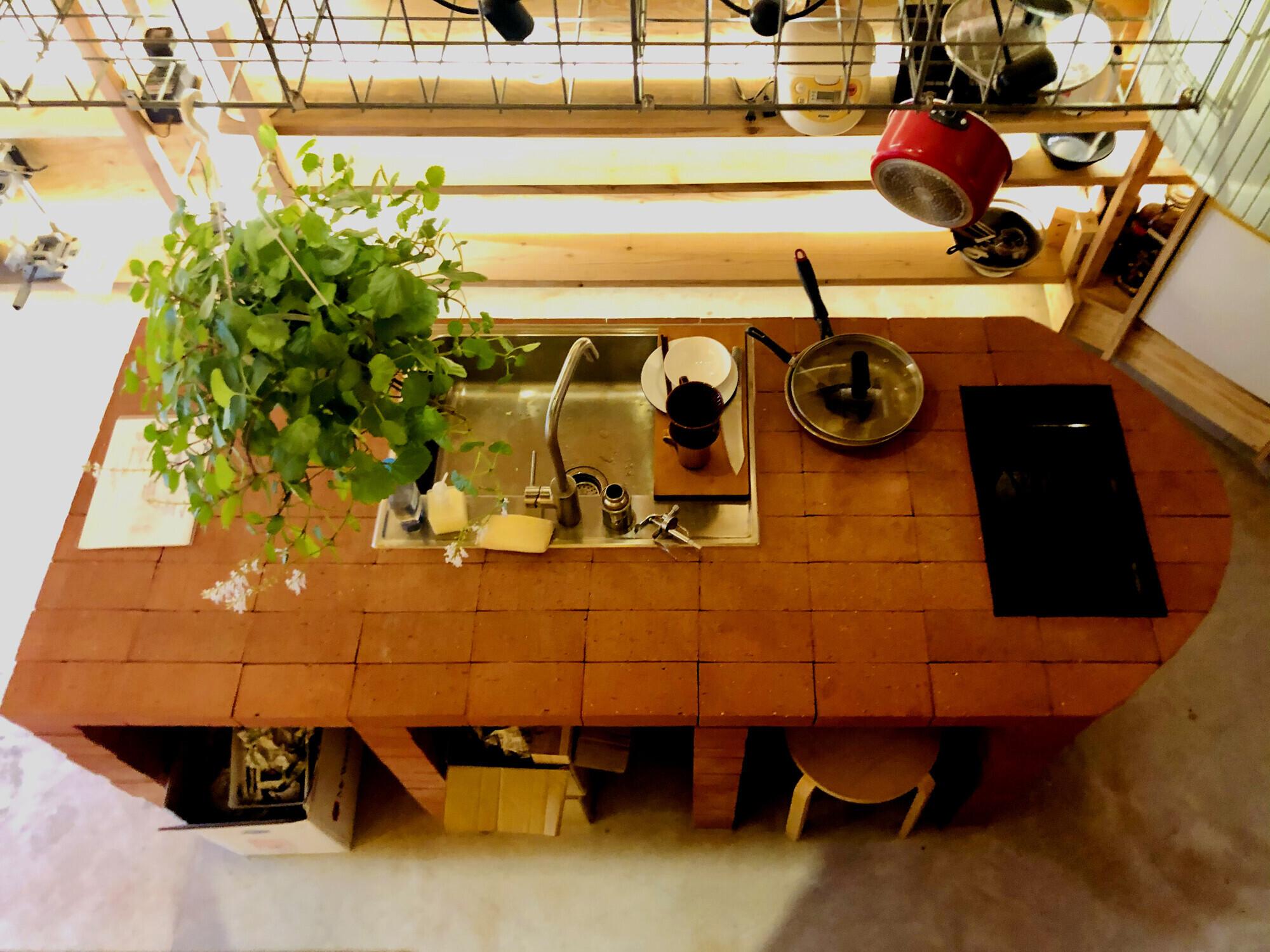 【キッチンカウンター】キッチンで作業する側の反対側は3席座るスペースがある。土間はモルタルなので床掃除はホースで水洗いできる。   せいかつとせいさくの家(美術家M邸)