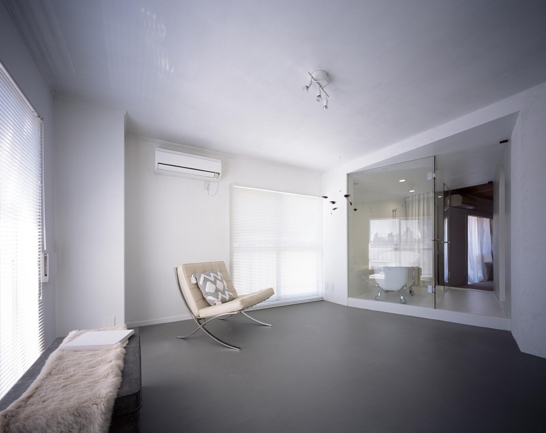 【室1】室1の奥には室2に繋がるトンネル(バスルーム)があります。使っていない時はカーテンを開けてガラス越しに室2が見通せます。写真:西川公朗 | 2つのトンネルのあるアトリエ
