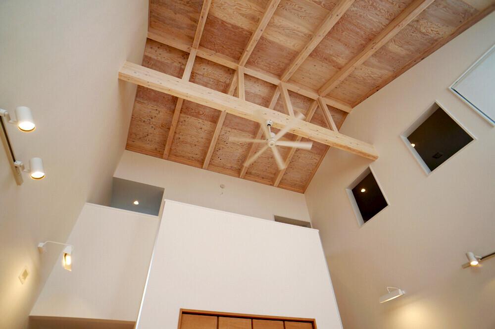 家の真ん中にある天井の高い開放的な吹抜け.吹抜け越しに左右でゾーンが分かれており,壁一枚の窮屈さがない.2階は左が子供部屋と右が予備室.1階は左にキッチン,右が主寝室. | 長期優良 + 大きな吹抜けをめぐる自由なガレージハウス