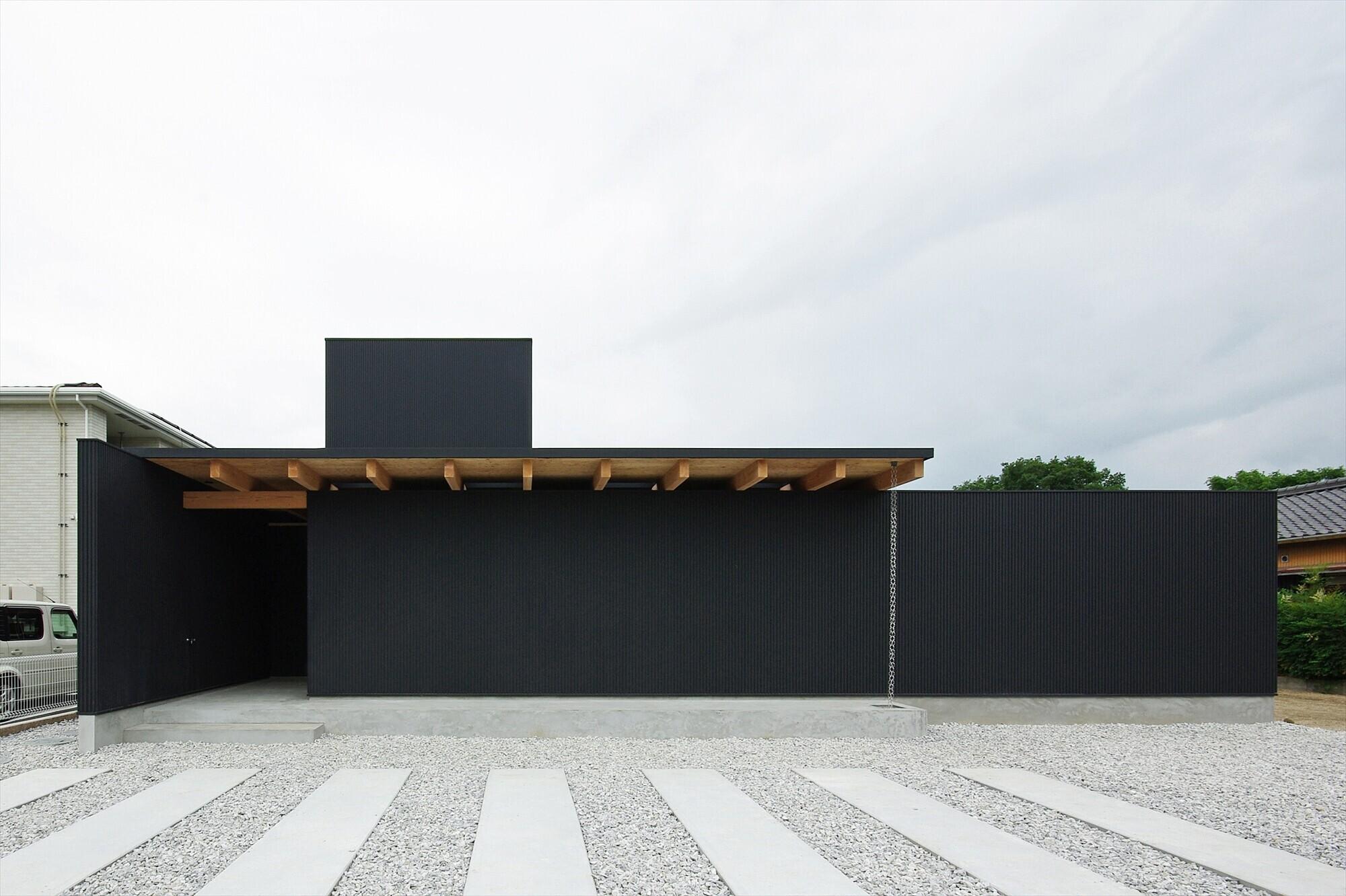 外壁はガルバリウム鋼板の八山葺き、色は黒。手前の壁と建物の間にはスペースがあり、モミジが植えられています。 | 上野の家-ueno
