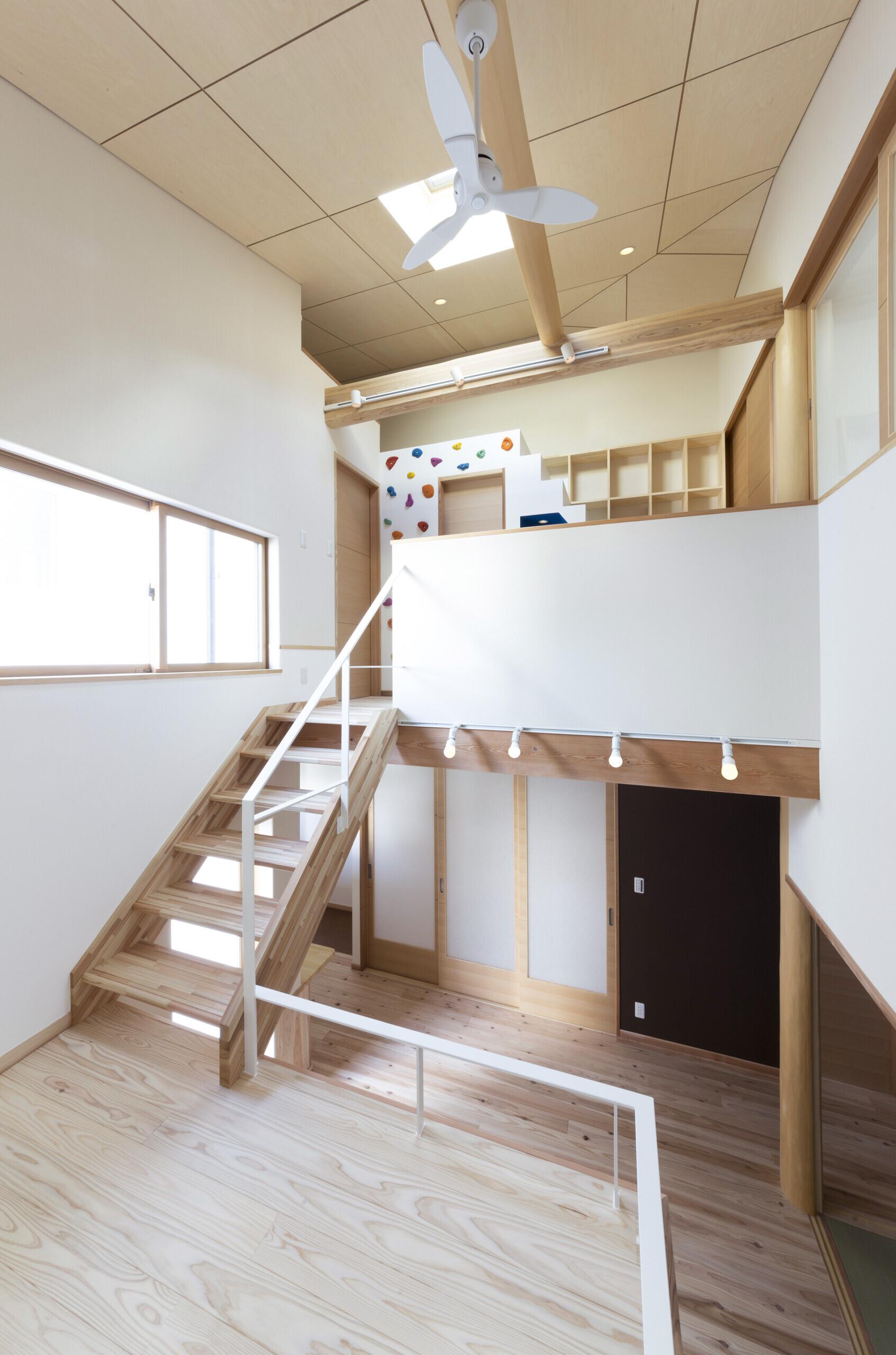 光のデッキを挟む家、吹抜けに光が差し込むリビングの建築事例写真