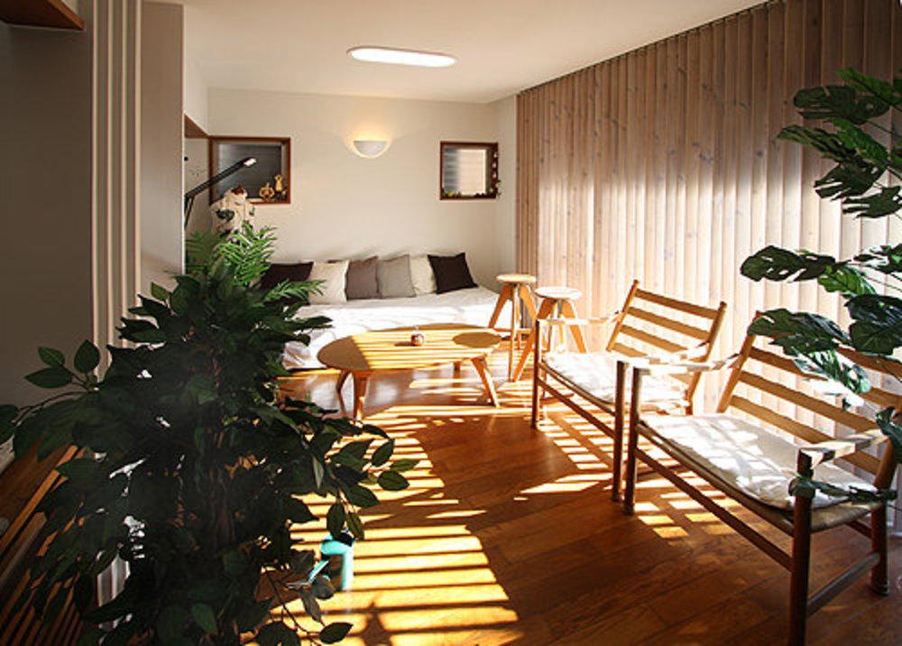 新たに居間に取付けた木製縦型ブラインドは、一日の陽の変化を日時計のように刻々と家の中に刻みます。  | 中庭のある家
