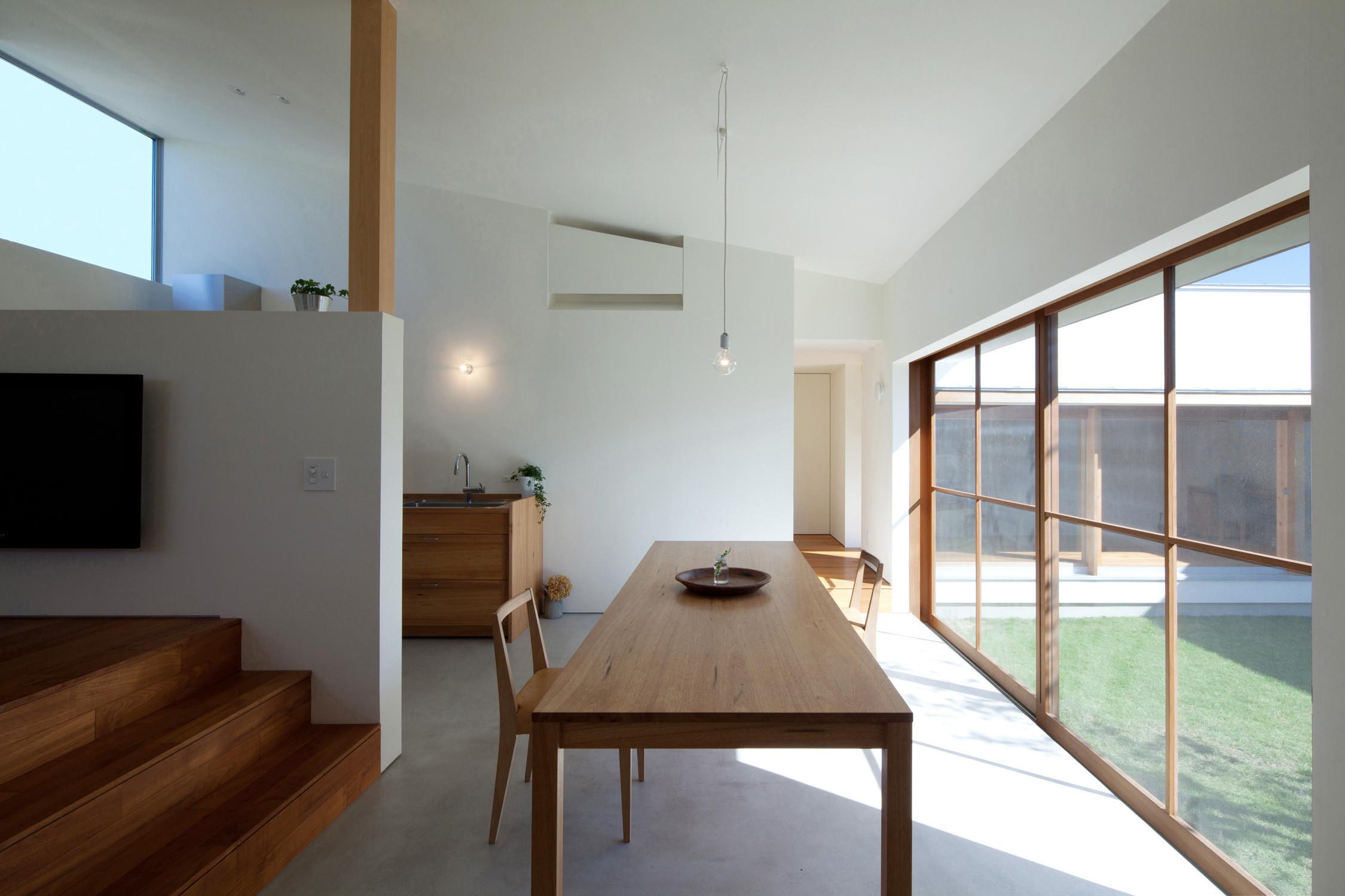 モルタル仕上げの食堂、台所。中心には大きなテーブルを配置。   海東の家/地に近い暮らし 平屋のコートハウス